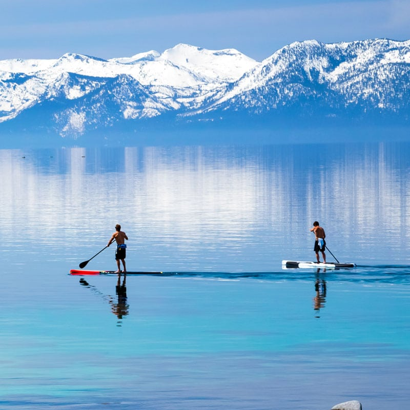 Two paddle boarders in the winter